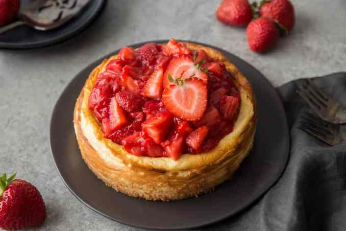 a keto strawberry cheesecake served on a black plate with strawberry garnish