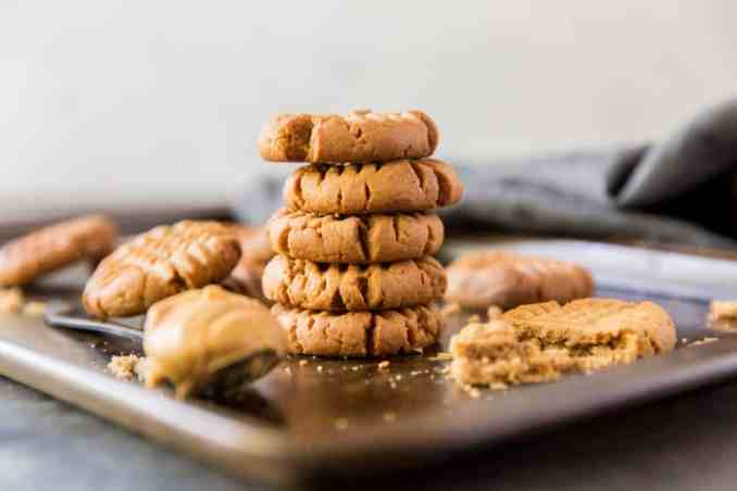 Cookies stacked on a baking sheet next to peanut butter