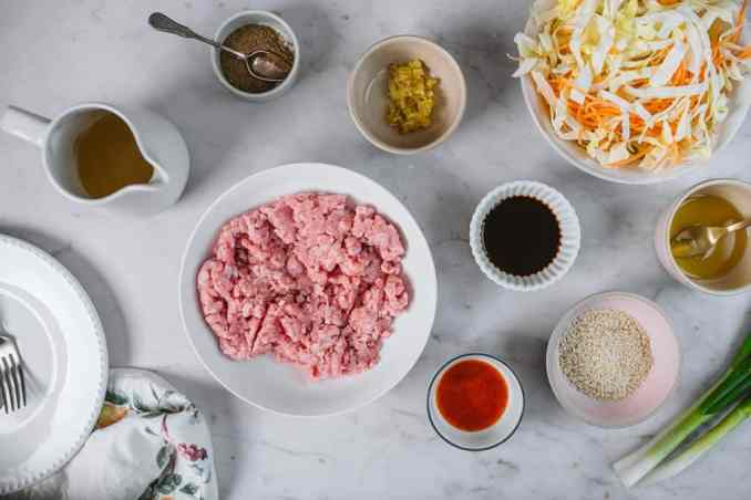 All the ingredients to make egg roll in a bowl inside white ceramic ramekins