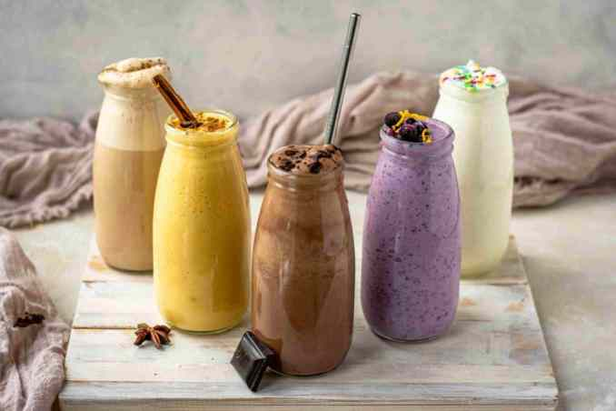 Five colorful jars of keto shakes lined up in a V formation