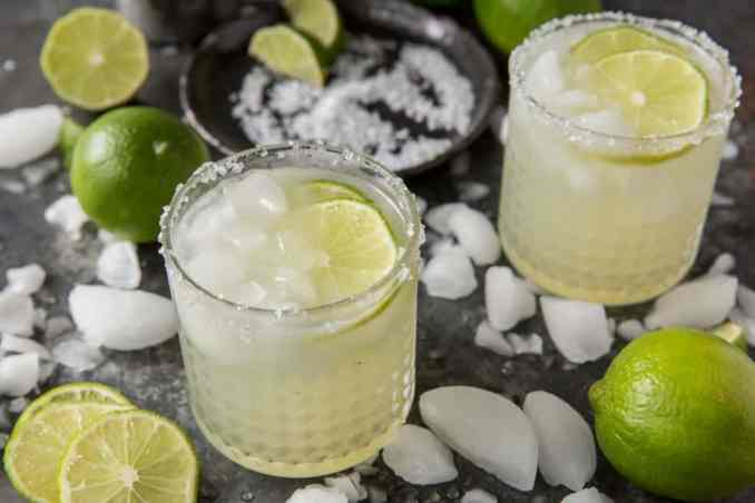 Prepared keto margaritas next to crushed ice and lime.