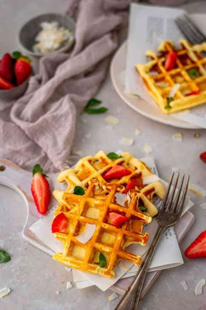 Two protein waffles on a cutting board topped with strawberries and mint.