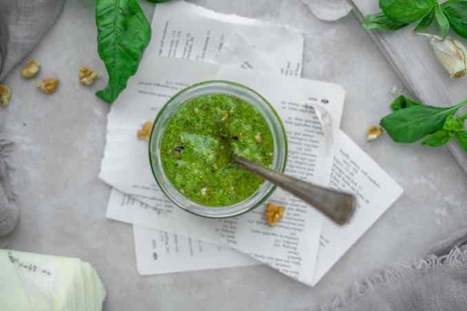 pesto dish on top of napkins with ingredients around