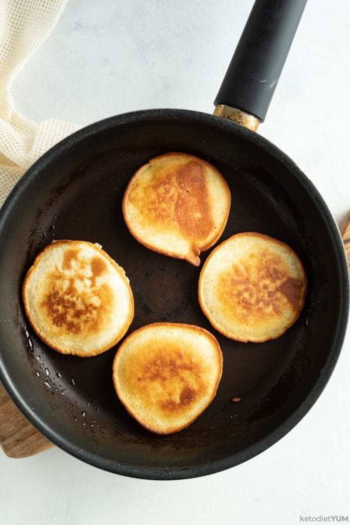 Golden brown keto pancakes cooked to perfection in a pan and ready to serve with cranberry sauce.