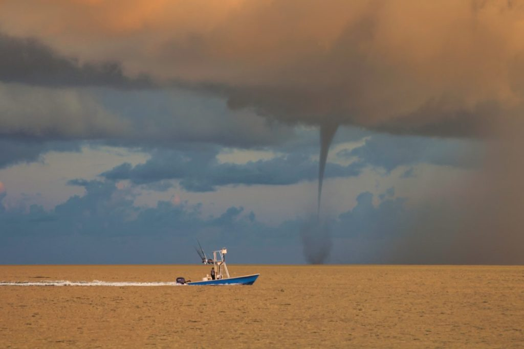 A Fishing boat passes in front of a waterspout at sunrise in the Gulf of Mexico just off Anna Maria Island, Florida.
