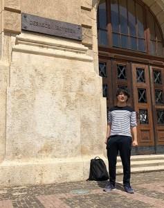 医科大学の建物の前に立つ、高松英会話ケビンズイングリッシュハウスの生徒