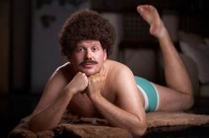 Aaron Merke in afro and underwear