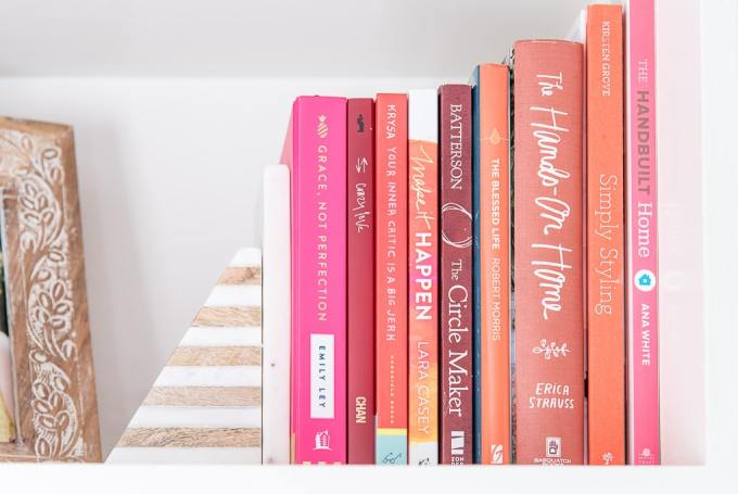 pink red and orange books on a shelf with a marble bookend