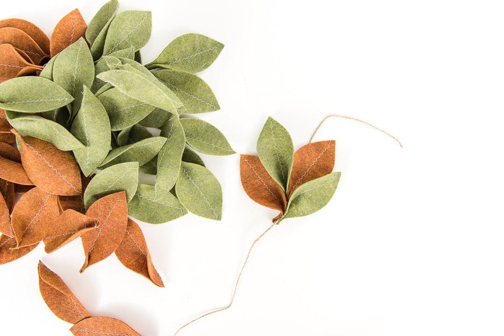 assembling felt magnolia garland green and tan leaves on jute cord
