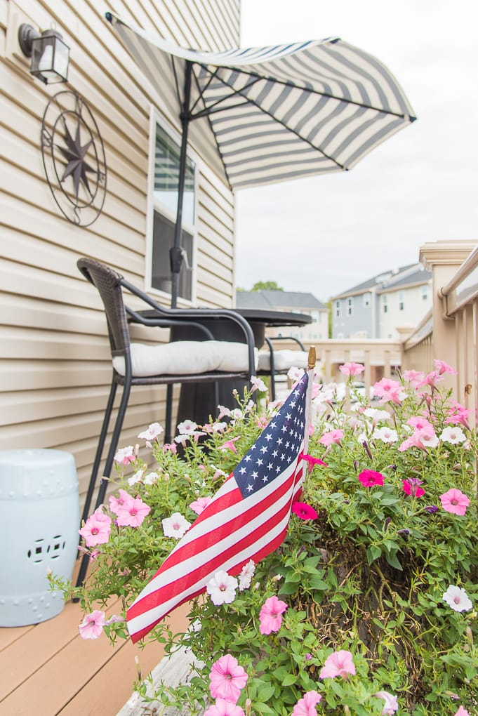 outdoor porch deck decorated for summer with flowers and American flag