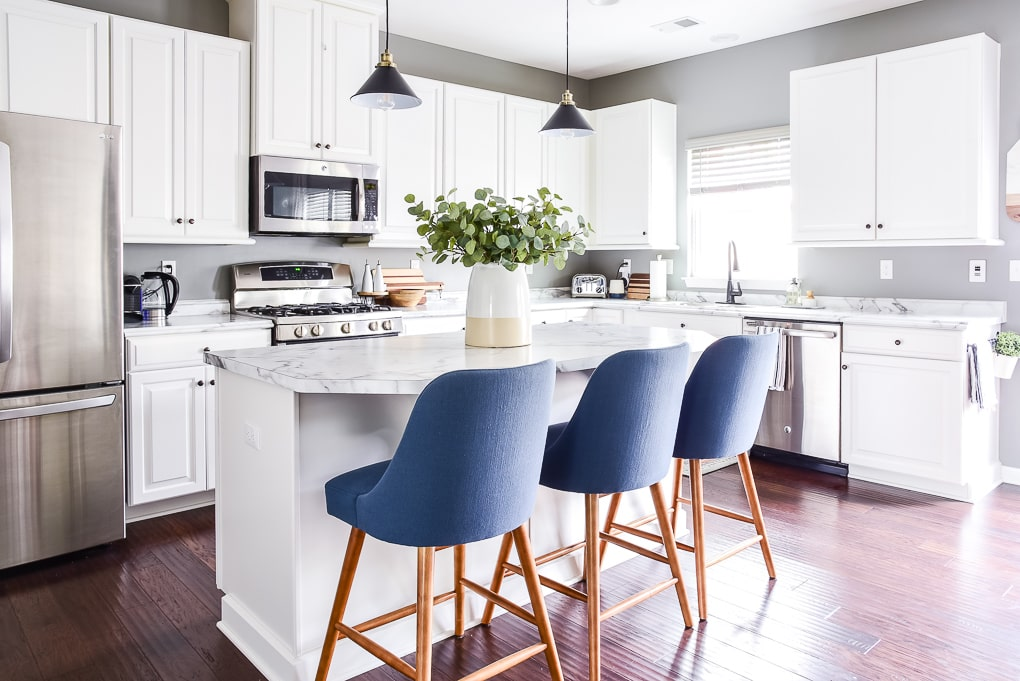 white kitchen with blue barstools and vase on the island