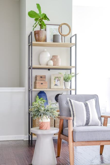 decorated book shelf behind living room chair