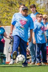 Student kicking soccer ball.