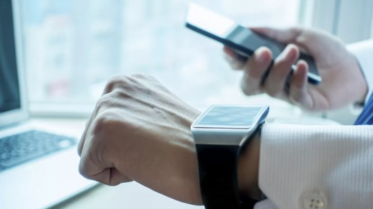 Businessman using his smartwatch and phone in office