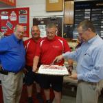 Boris Dover cuts the cake as Johnny, Ronny and Bobby look on
