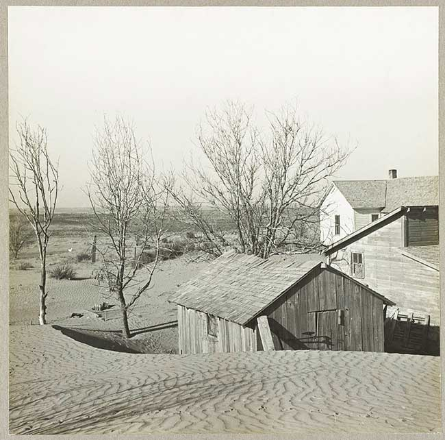 Black and white photo of farmstead overcome by sand dunes.