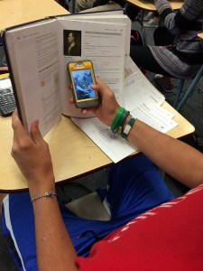 photo of student hiding mobile device inside textbook