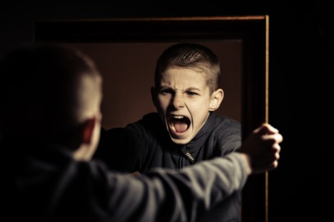 angry child holding mirror and yelling