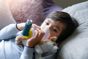 boy lying in bed using inhaler for breathing treatment
