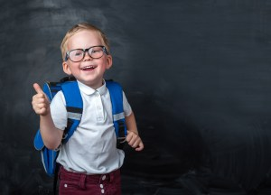 Happy smiling boy in glasses with school bag