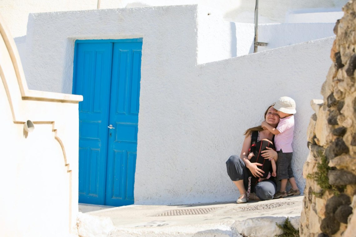 mom and son in street of Santorini resting