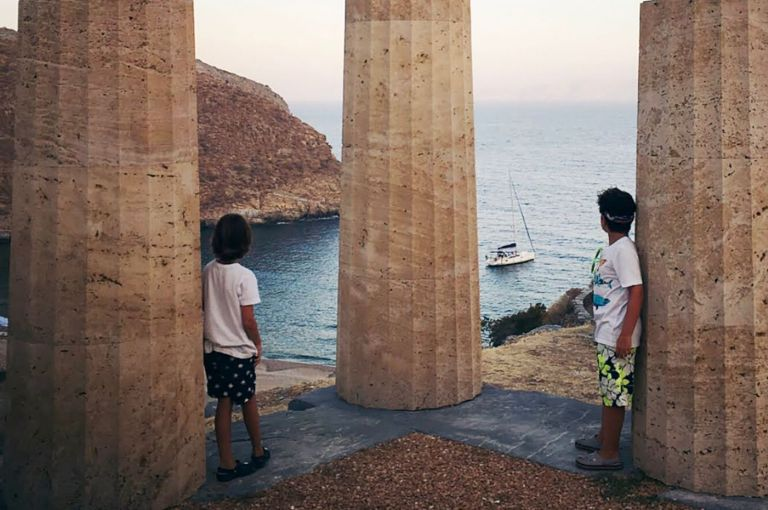 Two kids standing next to ancient Karthea ruins