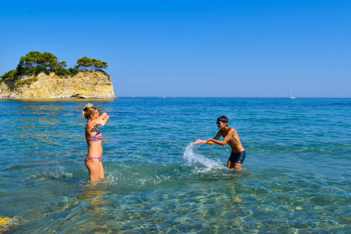 family playing in sea greece