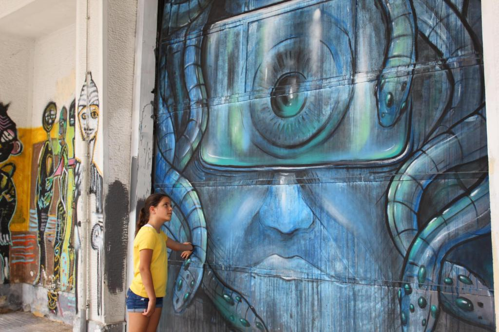 girl looks a grafiti during street art tour in Athens