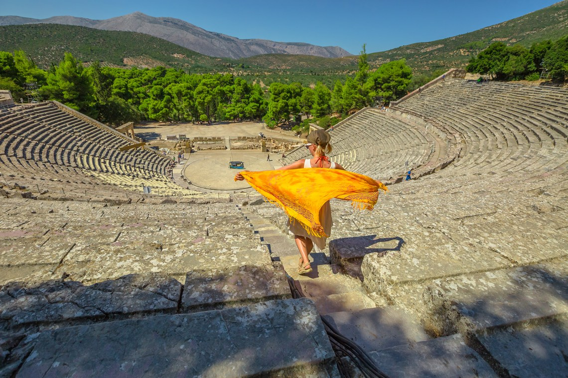 Woman walking downstairs the Ancient Theatre Epidaurus amphitheater in Peloponnese, Greece. Historical heritage and landmark. European travel destination.