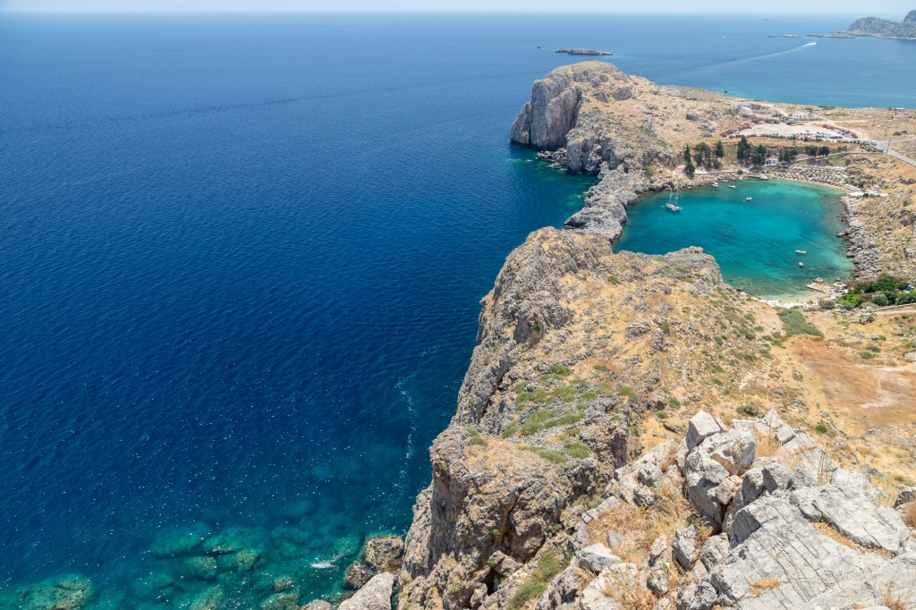 Scenic view from the acropolis of Lindos at the coastline of the mediterranean sea and St. Pauls bay