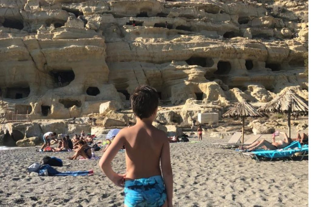 A boy looking at Matala Caves in Crete MT