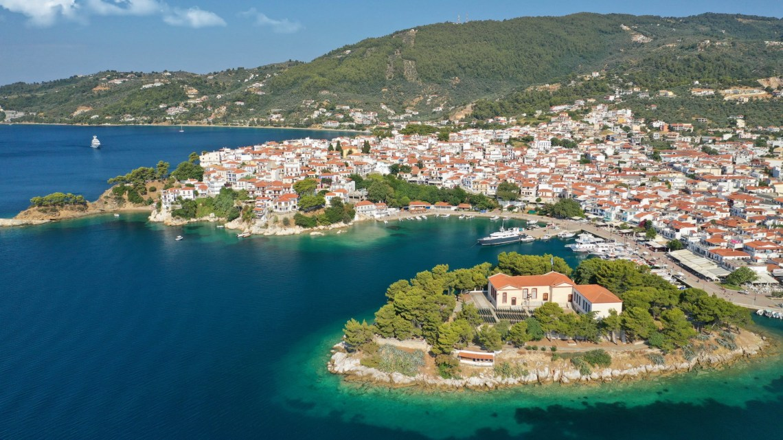 Aerial drone photo of amazing vegetated islet of Bourtzi built in small peninsula in port of Skiathos island main town hosting an old school, Sporades, Greece SH-min