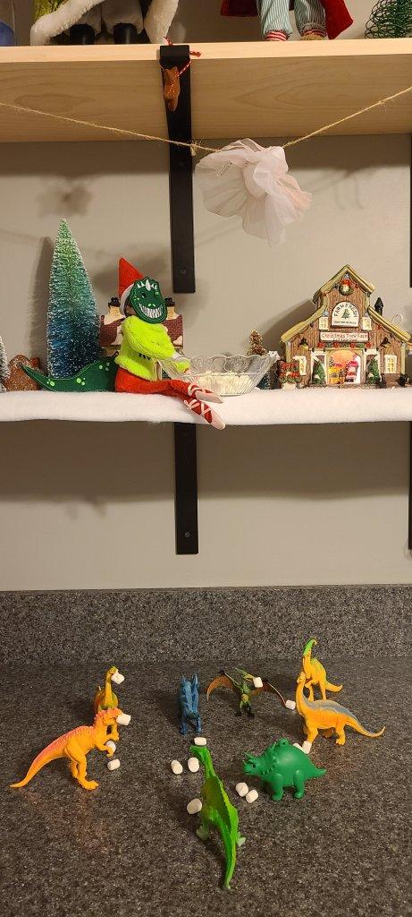 elf on the shelf feeding dinosaurs