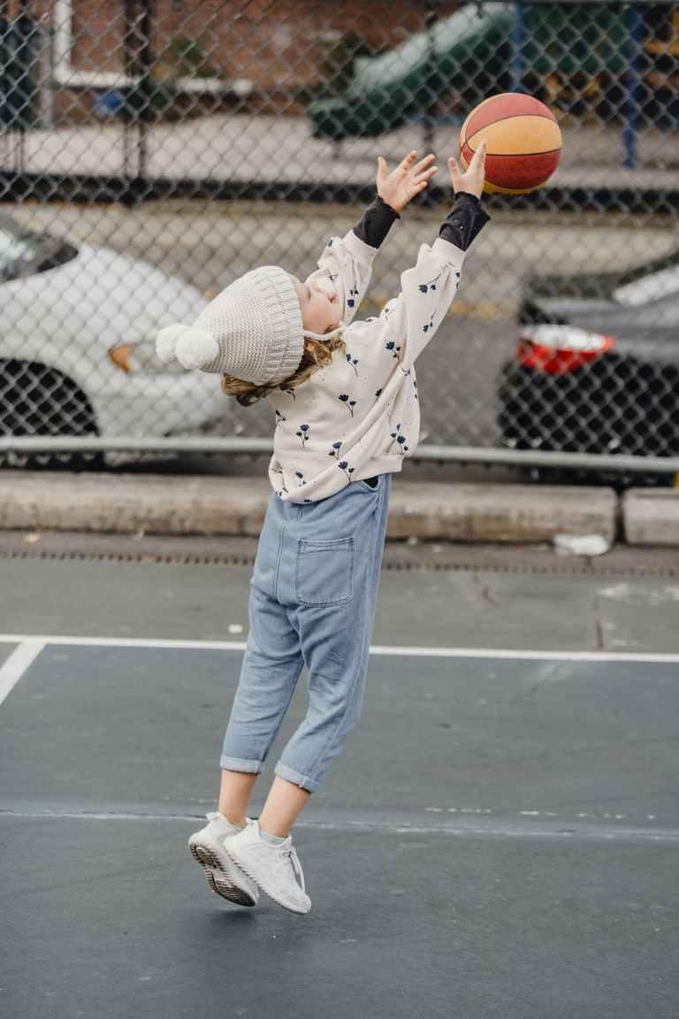Petite fille qui lance un ballon de basket