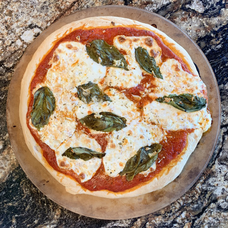 4 ingredient margherita pizza on a marble counter and pizza stone
