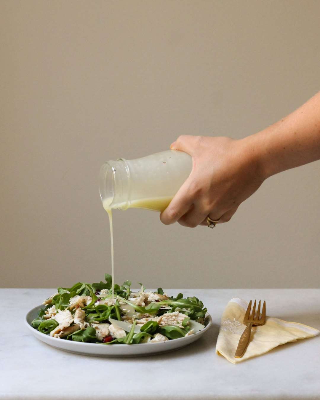 Lemon vinaigrette dressing being poured onto an arugula salad