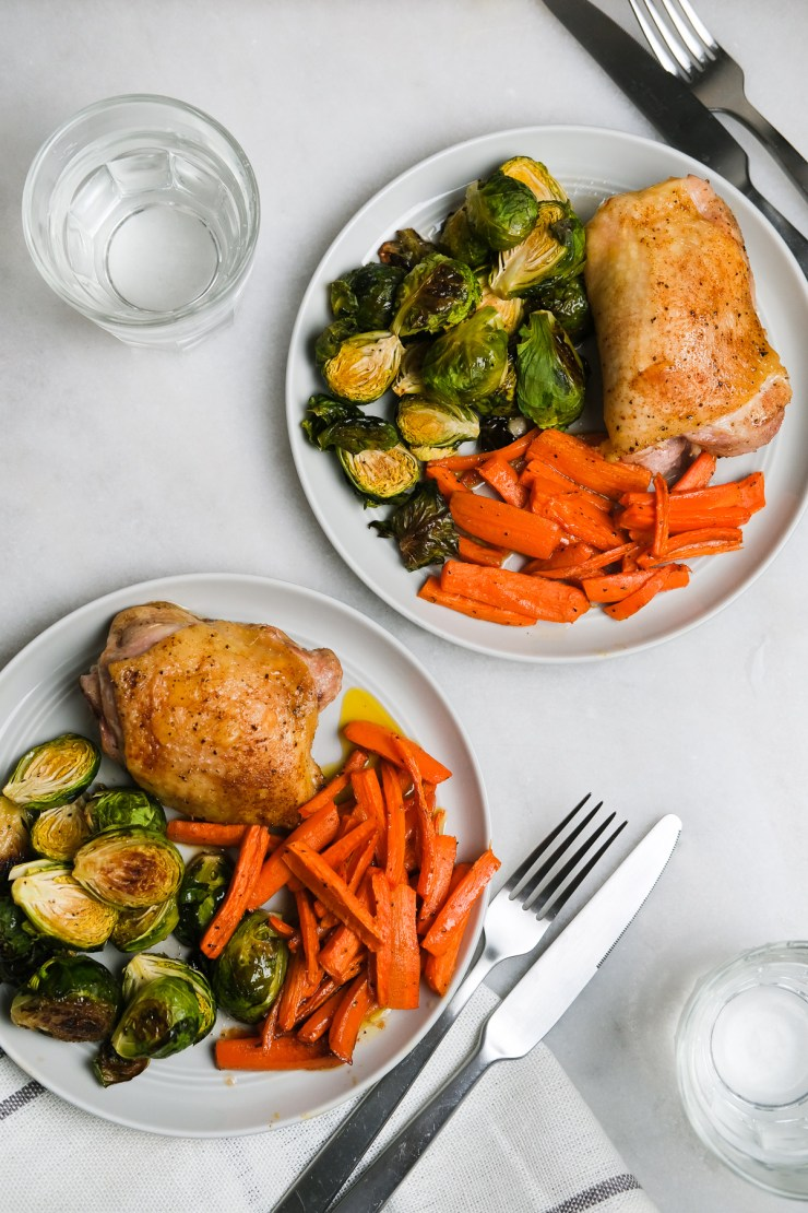 chicken thighs with roasted vegetables on plates ready to eat