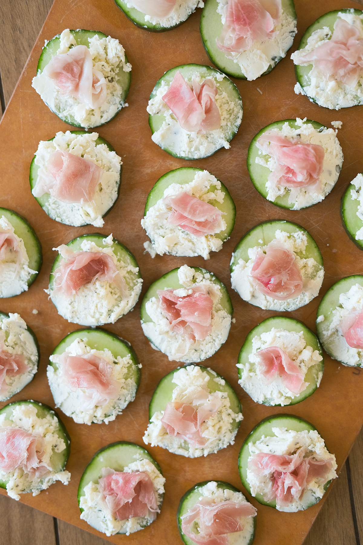 prosciutto cucumber bites on a cutting board
