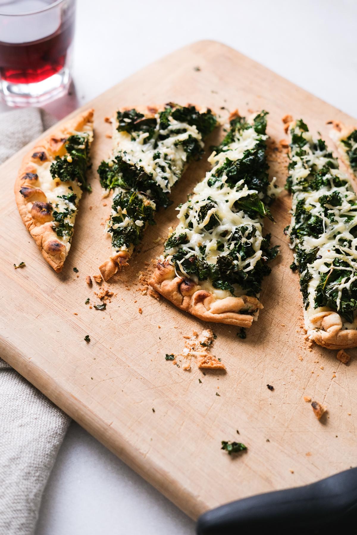 kale parmesan flatbread cut into individual slices