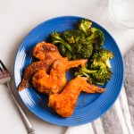 crispy oven baked buffalo wings on a blue plate with broccoli