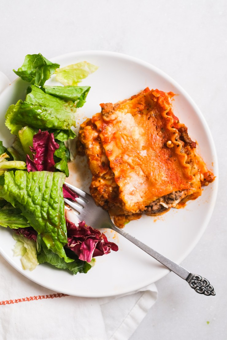 slice of cottage cheese lasagna with side salad on a white plate