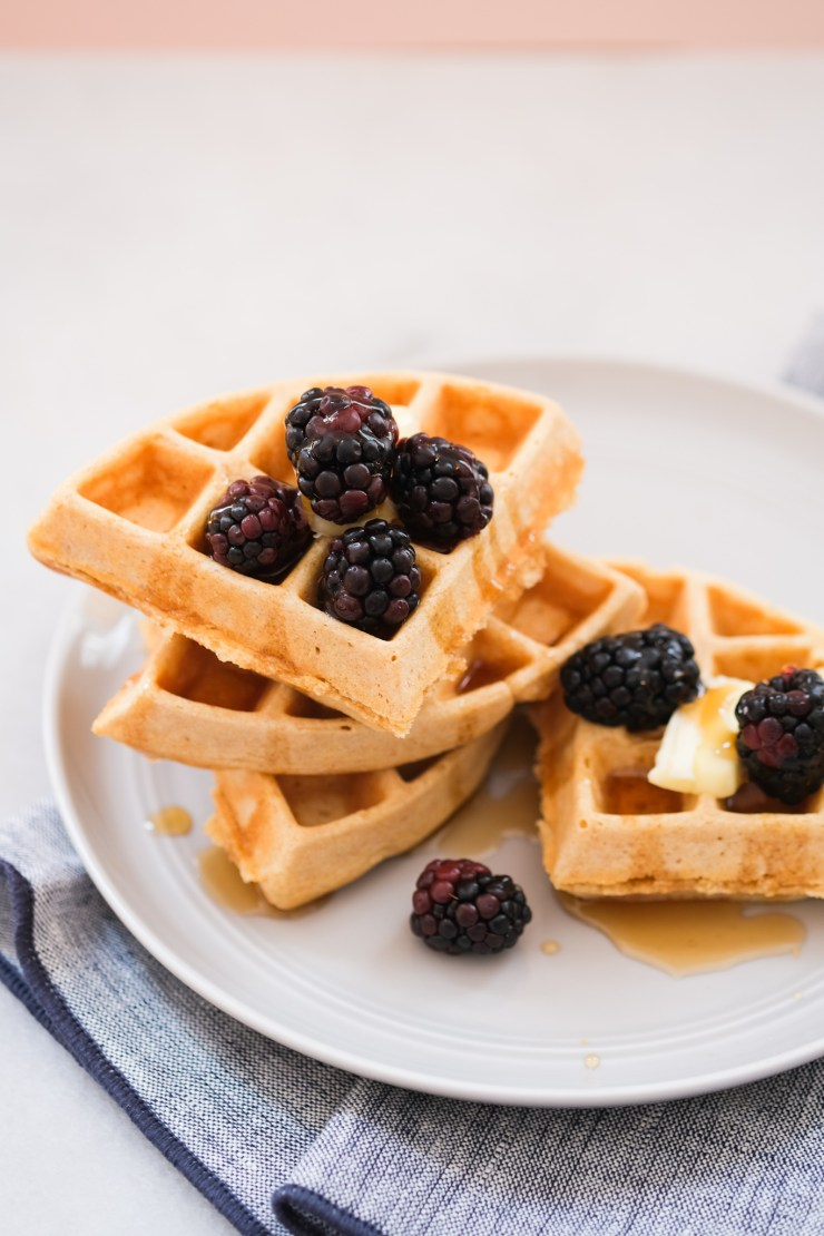 stacked whole wheat waffles with berries and butter