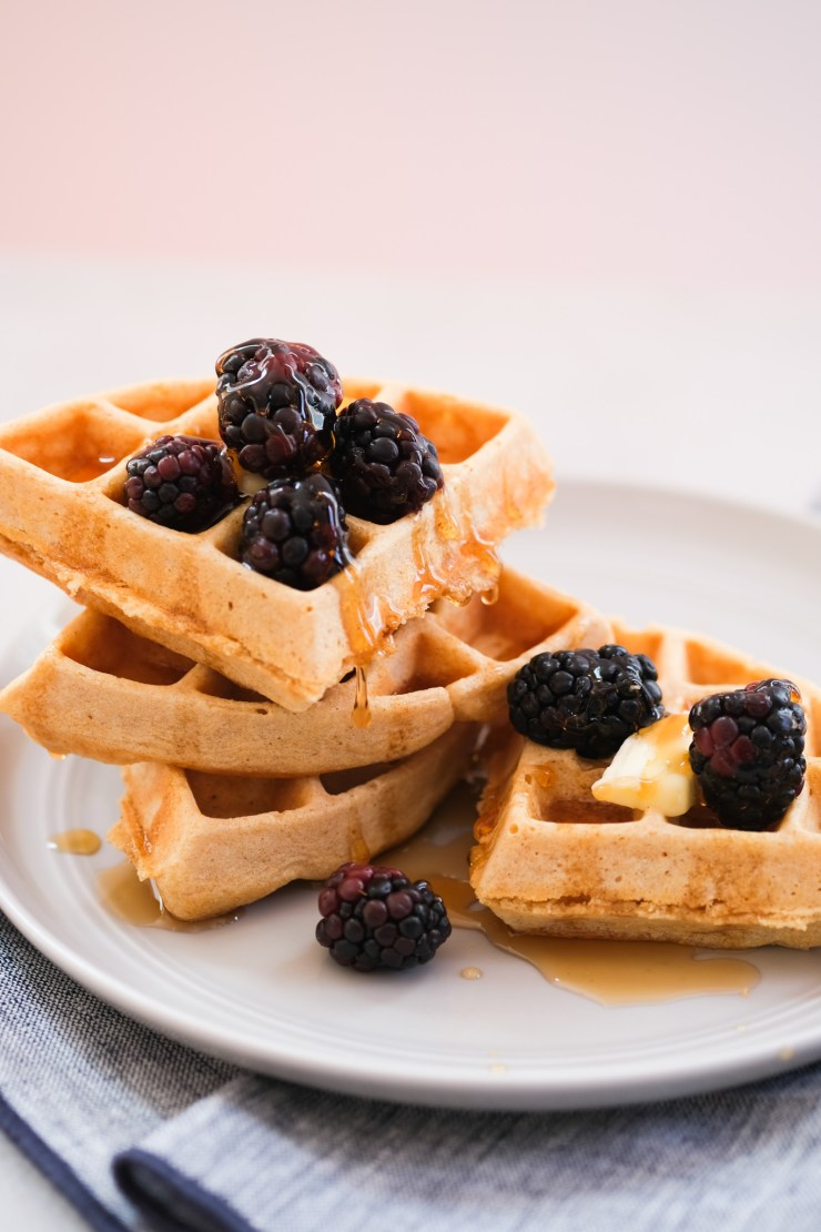 whole wheat waffles dripping in maple syrup