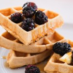 whole wheat waffles on a grey plate with drizzled maple syrup