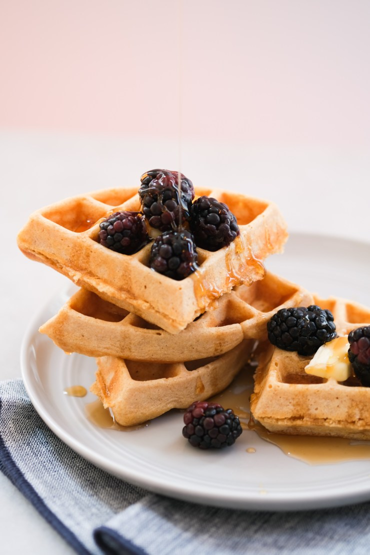 drizzling maple syrup on a berry with whole wheat waffles
