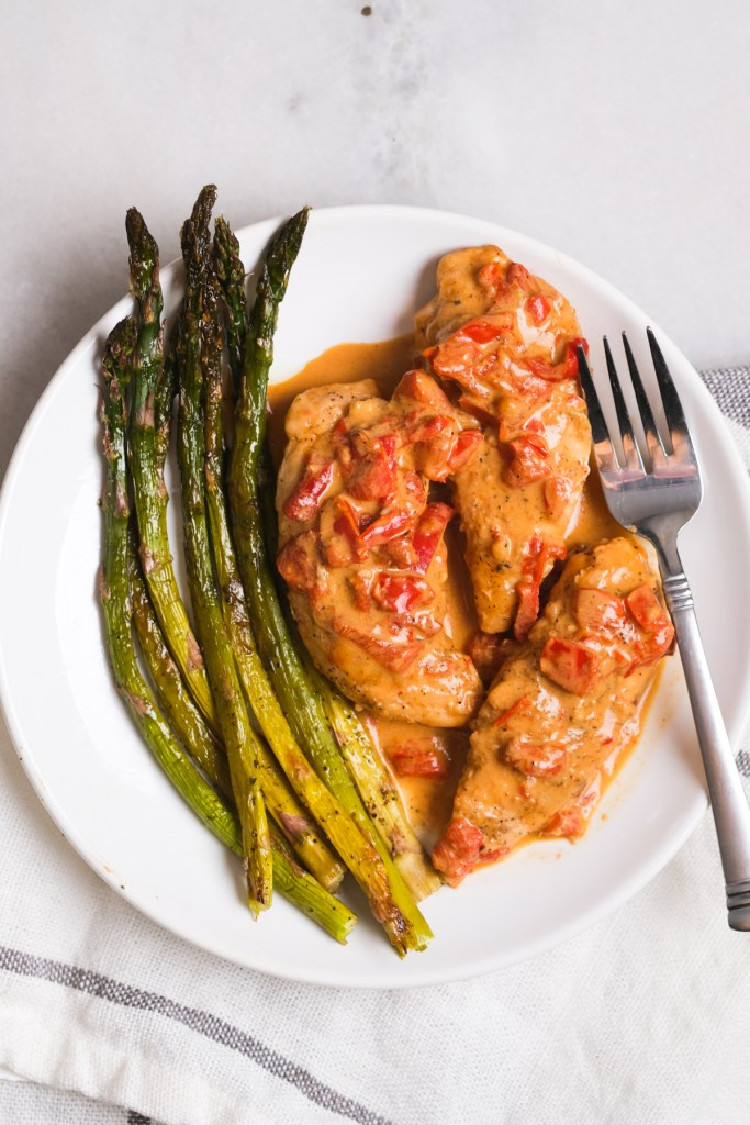 creamy roasted red pepper chicken with asparagus on a plate