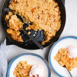 apple pear crisp in a cast iron skillet with bowls