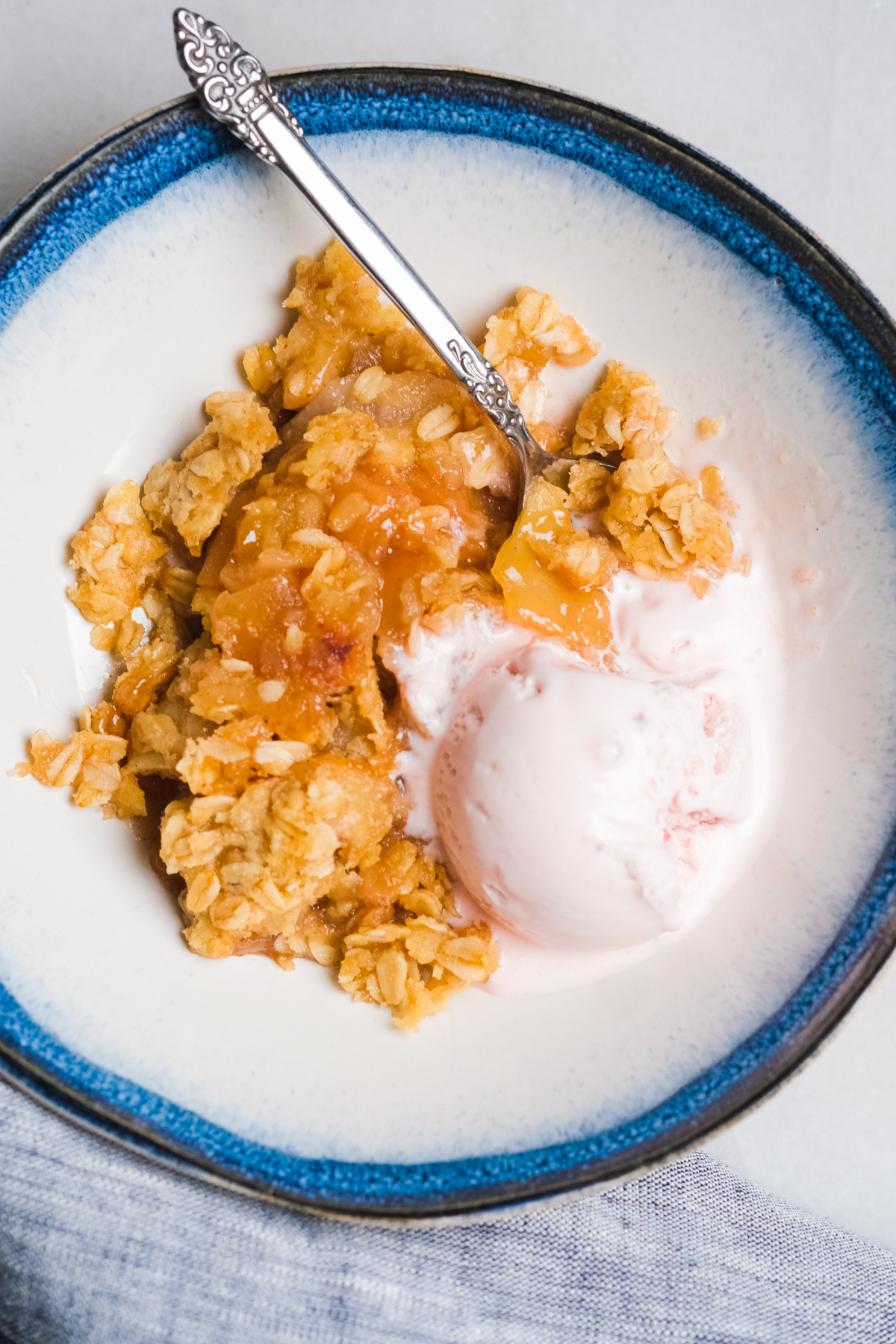 apple pear crisp in a bowl with strawberry ice cream