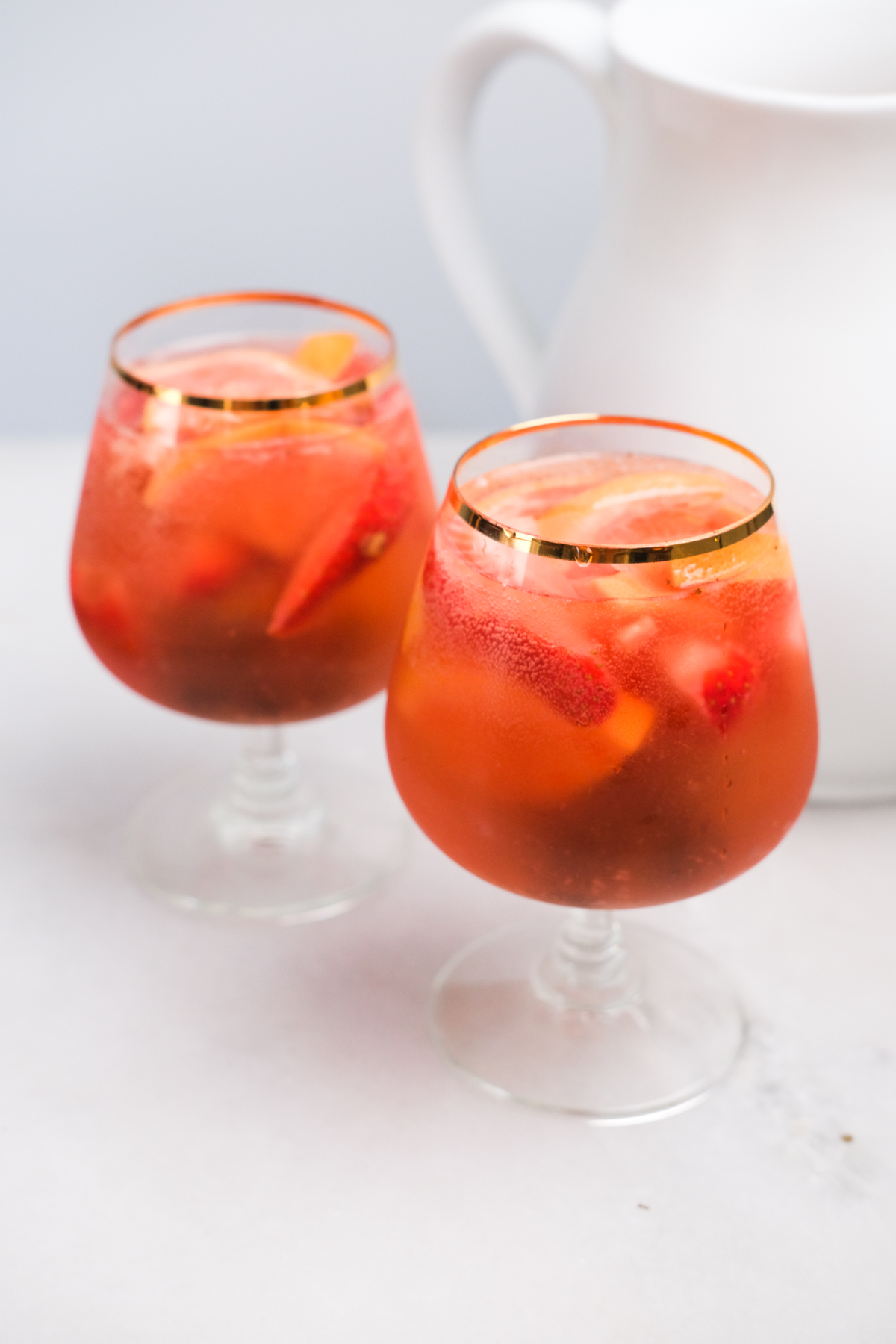 two glasses of rose sangria with a pitcher