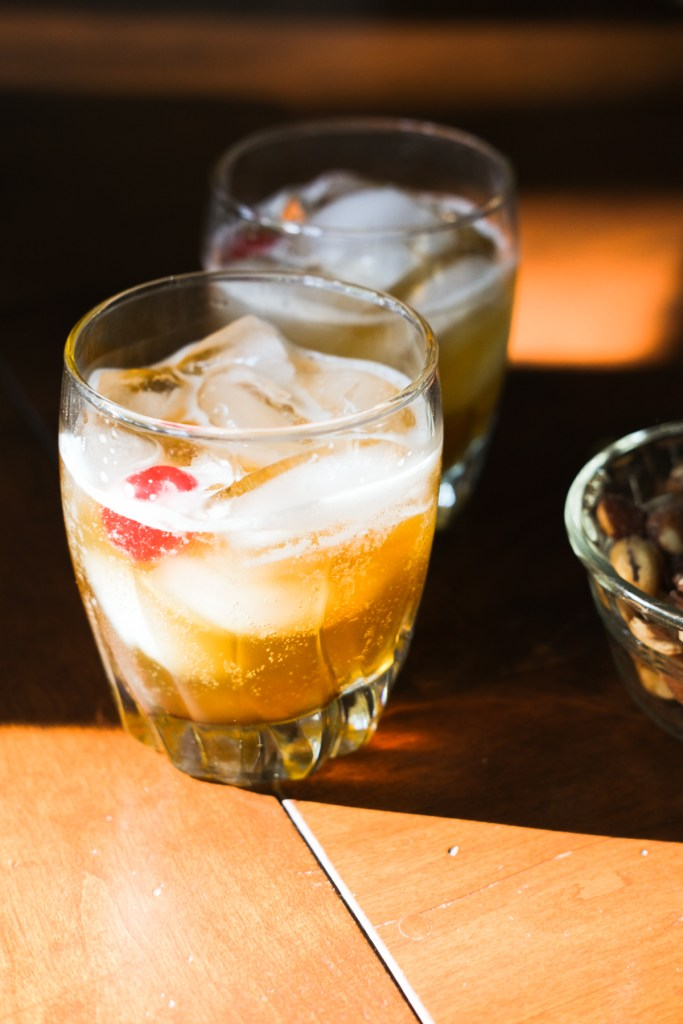 two glasses of amaretto sour on a table